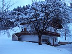 front of the Chalet in winter time with Chrismas light on balkoni