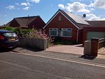Front of Bungalow with large drive with parking for 2 cars
