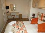 Principal en-suite double bedroom with walk-in closet, dressing table, mirror and TV