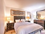 The master bedroom boasts a plush queen-sized bed and gorgeous wood furnishings.