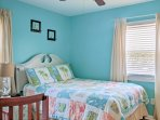 The second bedroom offers a queen-sized bed and calming blue colored walls.