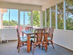 Sip your morning coffee or enjoy breakfast in the screened-in porch with a table set for 6.
