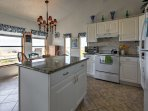 The spacious, fully equipped kitchen features granite countertops and a center-island, providing enough space to...