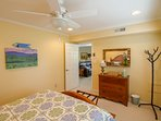 Queen bedroom includes place for luggage, ceiling fan and lots of natural light.