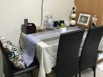 Black glass dining table with table cloth and chairs. Accented with a nice painting from Hawaii.