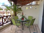 large balcony with dining table and chairs, gas grilll