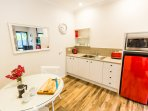 Kitchenette with fridge, microwave, toaster, jug & crockery