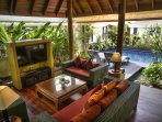 Delightful open plan tropical living area looks out to the pool