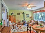 The cozy living room features comfortable furniture and a dining table set for 4.
