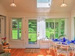Just off of the sunroom is a covered deck with patio furniture.
