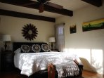 Master bedroom queen size bed with morning sun