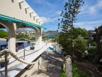 View from staircase overlooking roofed porch, pool and Spanish water