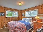 The second bedroom features shiplap walls and a queen-sized bed.
