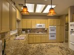 The fully equipped kitchen features granite counters, a stove, dishwasher and more.