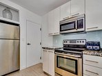 Convenient kitchen has a full-sized ref, microwave, coffee maker, and a few pantry items