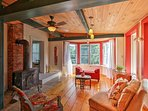 Wood beams accent the rear living room with a wood-burning stove, 2 sitting chairs, and a charming bench seat.