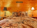 The large queen mattress with a wild tiger print along the covers in the upstairs bedroom.