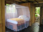 The bed with its mosquito net is made from recycled benches