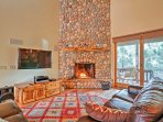 The living room boasts a stone fireplace, flat-screen TV and leather couches.