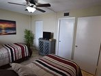 Second bedroom offers two twin beds with private bath access.