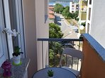 balcony with table and chairs, ocean view, street view