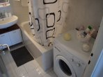 bathroom with washing machine, tub, shower, sink, toilet