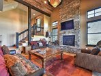 The stunning living room features vaulted ceilings, a beautiful gas-burning fireplace, inviting leather furniture and a...