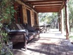 A wide sunny veranda with fold down daybed, overlooks the shallow clear waters of the Goulburn River