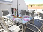Large first floor decked terrace, glass balustrade,views to beaches, seating and dining furniture.