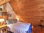 The second bedroom offers rustic wood ceilings and a full-sized bed.