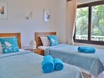Twin room has private furnished terrace overlooking the pool and garden
