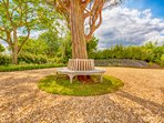 Teak tree seat at the entrance to Whitley Coach House