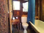 Rustic bathroom at rear of the cottage - with full claw foot bath, shower and flush toilet