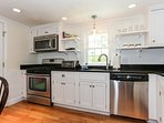 This cottage-style kitchen is fully equipped with stainless steel appliances and granite counters
