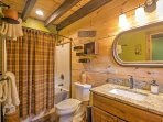 The wood beams continue into the bathroom, which features a shower/tub combo.