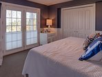 The master bedroom with a  king sized bed and lake view.