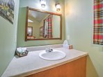 The bathroom offers bright lighting and plaid curtains.