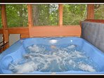 Hot tub on large screened in porch.