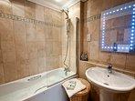 The limestone tiled family bathroom has a whirlpool bath