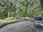 Nestled in a tropical setting, this home offers a large rear deck with views of the lush forest plants.