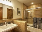 Each bathroom has been updated with decorative stone and frameless glass enclosures.