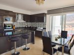 Open plan kitchen with breakfast bar, dining area and balcony