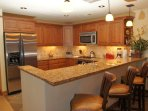 The kitchen features Granite counters & stainless steel appliances, including a gas range