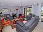 Indoor sitting area with wood burning fire, TV, DVD & CD players, games & book library.