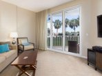 Lovely View of the green space and palm trees from this living room with 10' ceilings.