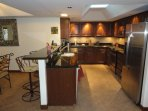 The kitchen is surrounded with granite counter tops. Behind is the laundry room and the garage door