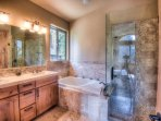 Master bathroom with jacuzzi-like tub and glass shower