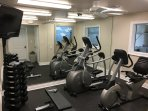 Fitness center with elliptical, exercise bike and weight bench with free weights.