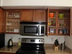 Upgrade stove with overhead cabinets and fully stocked flatware.
