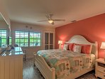 The master bedroom features beautiful furniture and decor, with views out onto the deck and the canal.